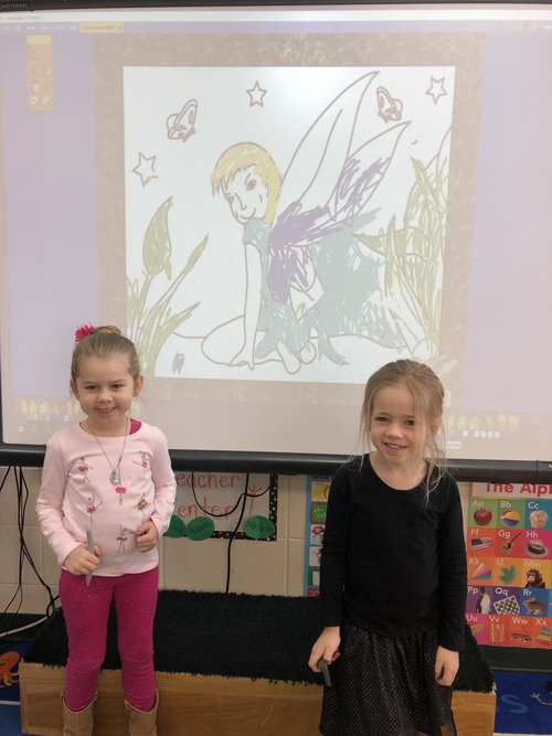 students coloring on the promethean board during play time